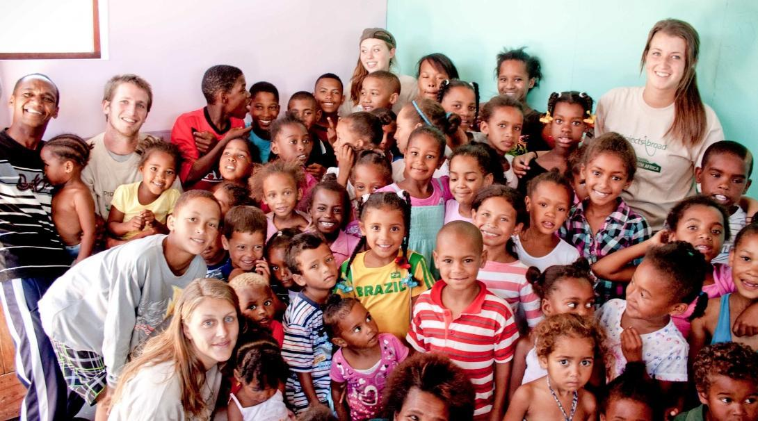 Childcare volunteers with children in South Africa pose for a group photo during a care and community project.